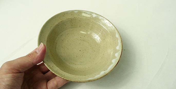 「道半の小皿-品番3(ベージュ・釉だれ和柄)」手に取った様子