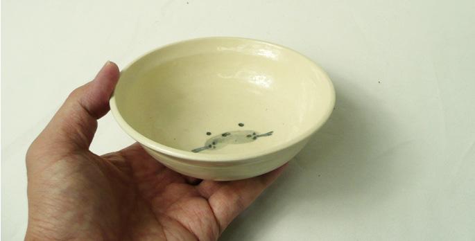 「道半の小皿-品番8(白・動物キャラ絵付き皿(アザラシ))」手に取った様子