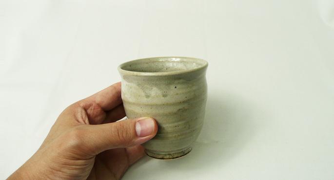 「釉だれちょこ/しぼり・グレー」お茶のコップ。手に持った様子